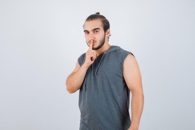 Junger mann im kapuzen-t-shirt, das schweigengeste zeigt und ernsthafte vorderansicht sieht.