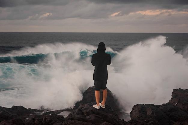 Junger mann im kapuzenpulli und in den kurzen hosen, die auf dem felsen nahe dem stürmischen meer mit hohen wellen mit schaum unter dem grauen himmel stehen
