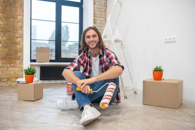 Junger mann im karierten hemd, der auf dem boden sitzt