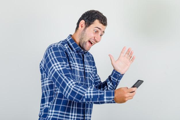 Junger mann im karierten hemd, der hand auf videoanruf winkt und glücklich schaut