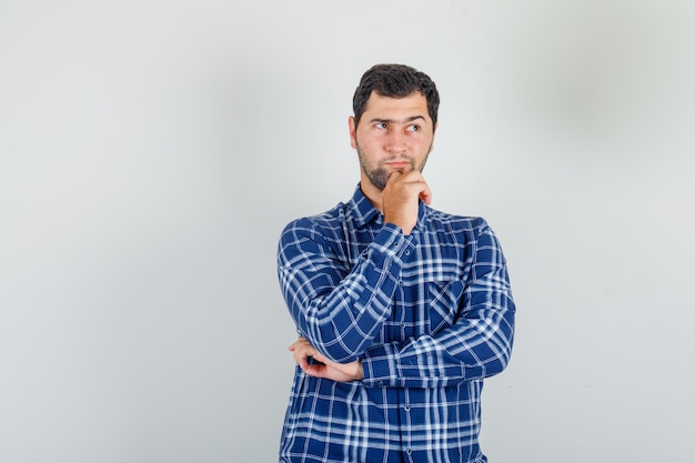 Junger mann im karierten hemd, der mit der hand am kinn denkt und gerissen aussieht