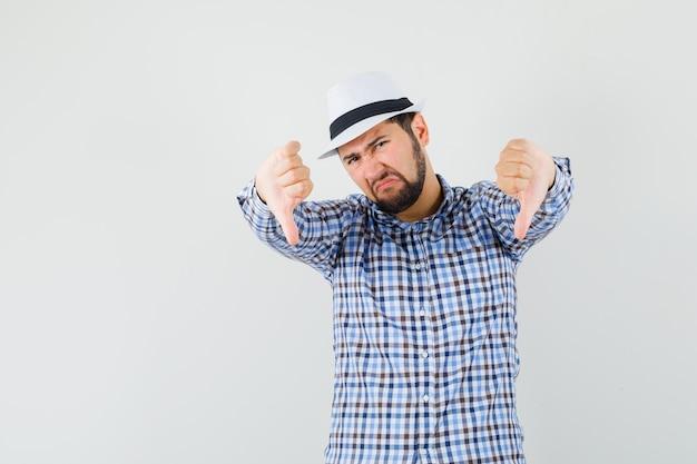 Junger mann im karierten hemd, hut, der doppelte daumen nach unten zeigt und unzufrieden aussieht, vorderansicht.