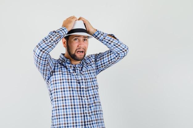 Junger mann im karierten hemd, hut, der hände auf kopf hält und unruhig schaut, vorderansicht.