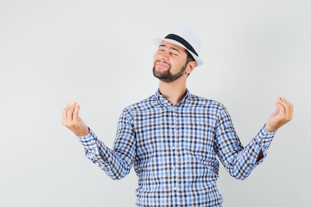 Junger mann im karierten hemd, hut zeigt italienische geste und schaut friedlich, vorderansicht.