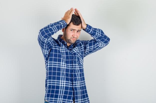 Junger mann im karierten hemd, kopf mit erhobenen händen haltend und erschöpft aussehend