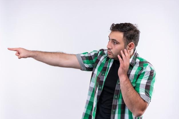 Junger mann im karierten hemd zeigt mit dem finger zur seite und sieht verwirrt aus, während er auf handy spricht, das über weißer wand steht