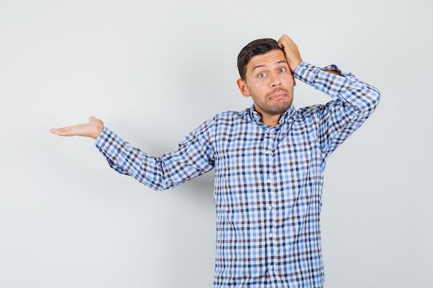 Junger mann im karierten hemd zeigt zur seite und sieht verwirrt aus