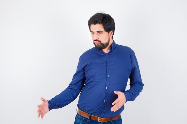 Junger mann im königsblauen hemd, das die größe von etwas zeigt, vorderansicht.