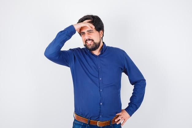 Junger mann im königsblauen hemd, das hand auf dem kopf hält, während er lächelt und fröhlich aussieht, vorderansicht.
