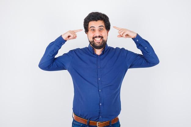 Junger mann im königsblauen hemd, der auf seinen kopf zeigt, während er lächelt und fröhlich aussieht, vorderansicht.