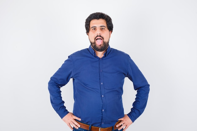 Junger mann im königsblauen hemd, der die zunge herausstreckt und seltsam aussieht, vorderansicht.