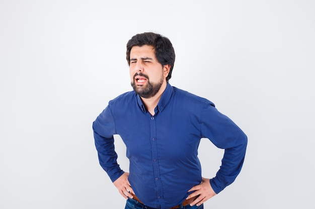 Junger mann im königsblauen hemd, der jemanden mit lauter stimme anruft, während er mit den händen auf der taille steht, vorderansicht.