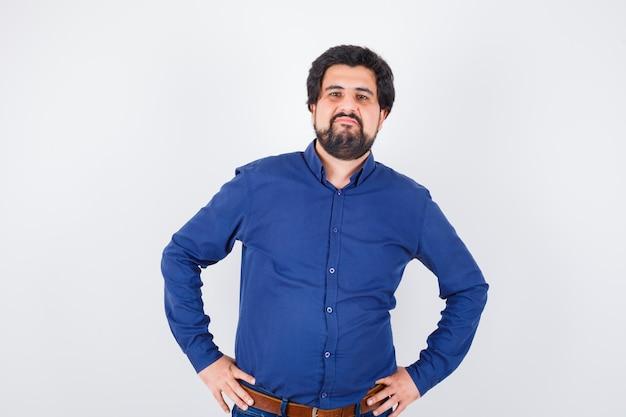 Junger mann im königsblauen hemd, der mit den händen auf der taille steht und unzufrieden aussieht, vorderansicht.