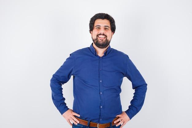 Junger mann im königsblauen hemd lächelt und sieht komisch aus, vorderansicht