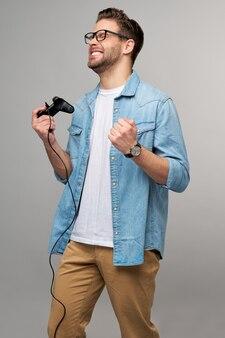 Junger mann im lässigen jeanshemd, der joystick oder gamepad hält, das spiel spielt