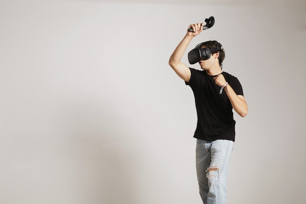 Junger mann im leeren schwarzen t-shirt, das golf oder tennis im vr-headset spielt, das etwas trifft, das auf weiß lokalisiert wird