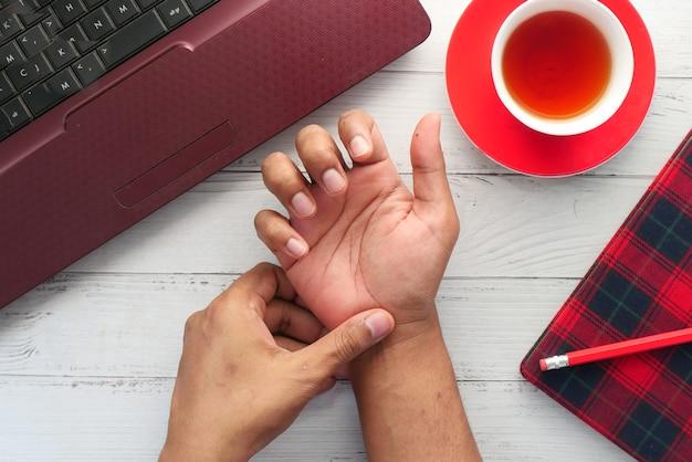Junger mann im leidenden handgelenksschmerz draufsicht.