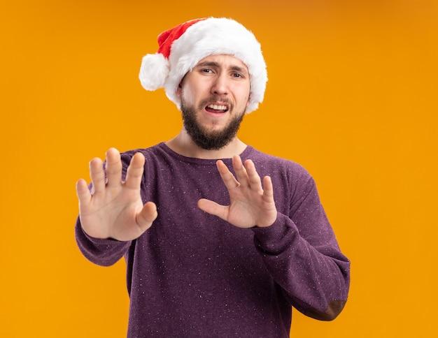 Junger mann im lila pullover und im weihnachtsmannhut, der kamera betrachtet, besorgt besorgt macht verteidigungsgeste, die hände heraus sagt, kommt nicht näher und steht über orangefarbenem hintergrund