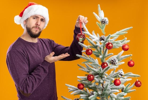 Junger mann im lila pullover und in der weihnachtsmannmütze, die neben weihnachtsbaum halten spielzeug hält, das es auf baum mit ernstem gesicht über orange hintergrund hängt