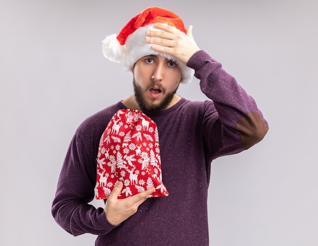 Junger mann im lila pullover und in der weihnachtsmannmütze, die rote tasche mit geschenken hält, die mit hand auf seinem kopf verwirrt schauen, vergessen, über weißem hintergrund zu stehen