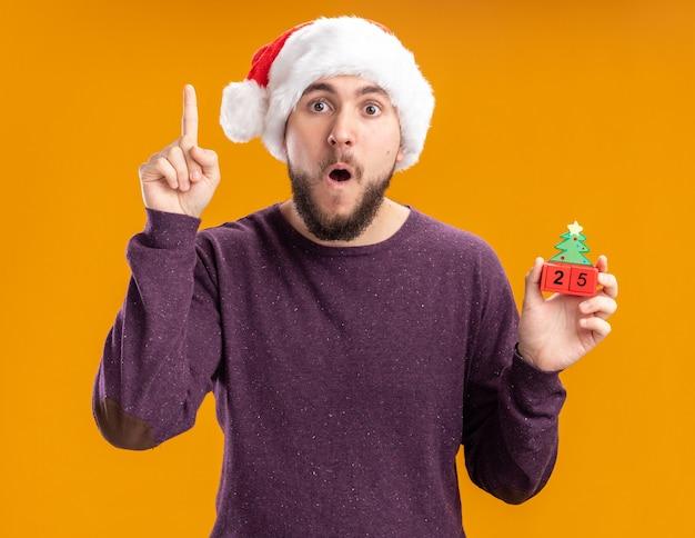 Junger mann im lila pullover und in der weihnachtsmannmütze, die spielzeugwürfel mit nummer fünfundzwanzig überrascht zeigt zeigefinger, der über orange wand steht