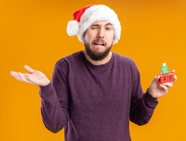 Junger mann im lila pullover und in der weihnachtsmannmütze, die spielzeugwürfel mit nummer fünfundzwanzig verwirrten und unzufriedenen achselzucken zeigt, die über orangeer wand stehen