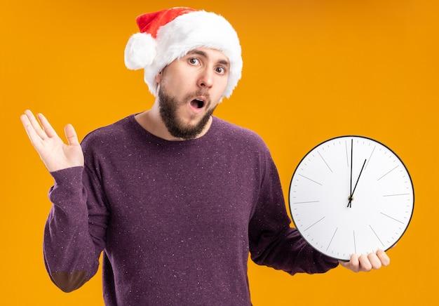 Junger mann im lila pullover und in der weihnachtsmannmütze, die wanduhr verwirrt und sehr ängstlich mit den schultern zuckend über orange wand hält