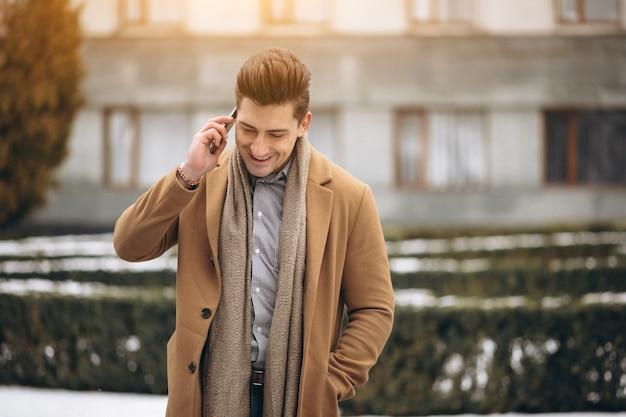 Junger mann im mantel draußen sprechend am telefon
