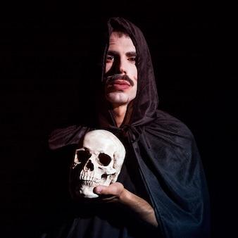 Junger mann im mit kapuze umhang, der schädel hält