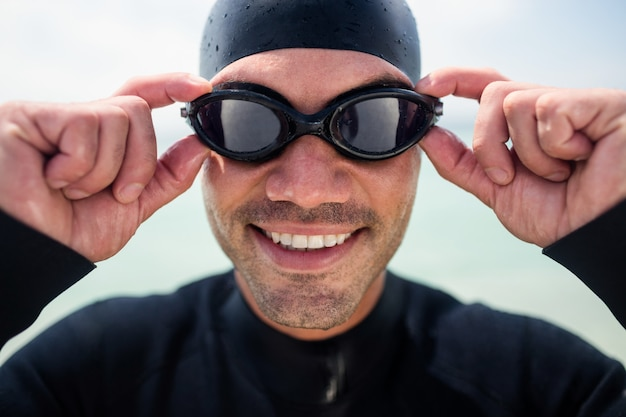 Junger mann im neoprenanzug und in schwimmbrille, die auf strand stehen