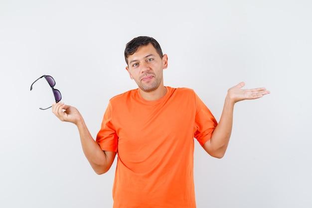 Junger mann im orangefarbenen t-shirt, das brillen hält und verwirrt schaut