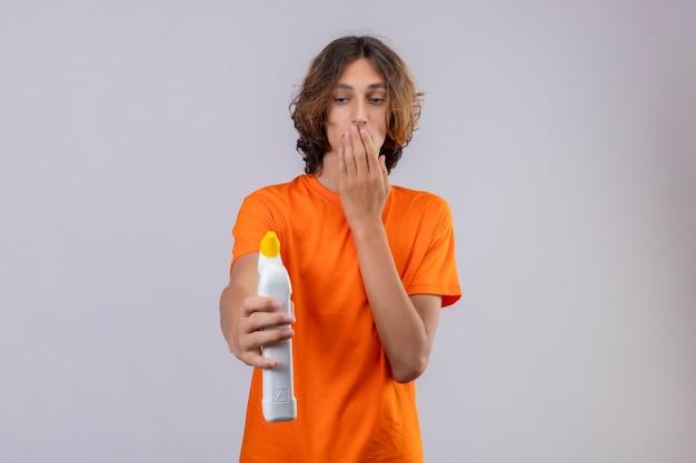 Junger mann im orangefarbenen t-shirt, das eine flasche reinigungsmittel hält, die es überrascht und erstaunt betrachtet, mund mit hand zu betrachten, die über weißem hintergrund steht
