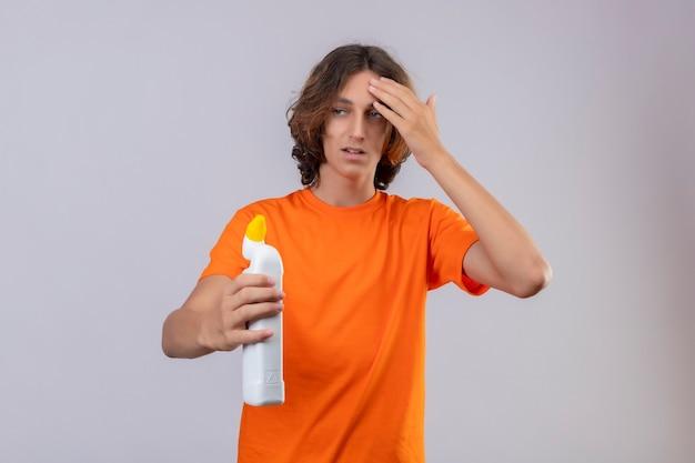 Junger mann im orangefarbenen t-shirt, das flasche reinigungsmittel hält, das verwirrt und überrascht über weißem hintergrund steht