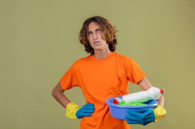 Junger mann im orangefarbenen t-shirt, das gummihandschuhe hält, die becken mit reinigungswerkzeugen halten, die mit nachdenklichem ausdruck auf gesicht denkend stehen über grünem hintergrund stehen