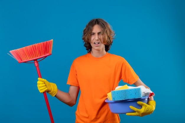 Junger mann im orangefarbenen t-shirt, das gummihandschuhe hält, die becken mit reinigungswerkzeugen und mopp halten, der genervt steht über blauem hintergrund steht