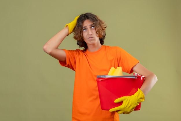 Junger mann im orangefarbenen t-shirt, das gummihandschuhe hält, die eimer mit reinigungswerkzeugen halten, die mit hand auf kopf für fehler suchen verwirrtes denken stehen über grünem hintergrund stehen