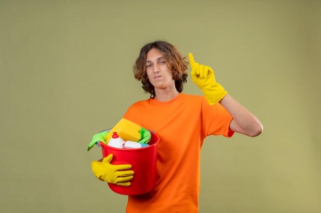 Junger mann im orangefarbenen t-shirt, das gummihandschuhe hält, die eimer mit reinigungswerkzeugen zeigen, die große idee haben, die zuversichtlich über grünem hintergrund lächelnd steht