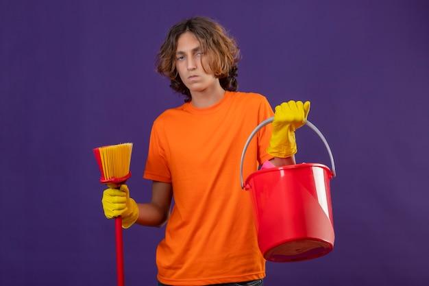 Junger mann im orangefarbenen t-shirt, das gummihandschuhe hält, die eimer und mopp betrachten kamera mit ernstem ausdruck auf gesicht stehen, das über lila hintergrund steht