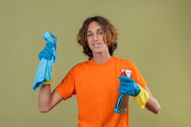 Junger mann im orangefarbenen t-shirt, das gummihandschuhe hält, die reinigungsspray und teppich betrachten, die kamera betrachten, die zuversichtlich über grünem hintergrund steht