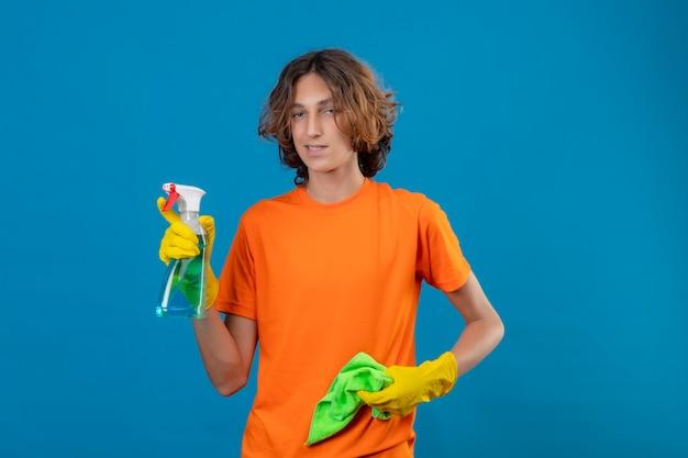 Junger mann im orangefarbenen t-shirt, das gummihandschuhe hält, die reinigungsspray und teppich betrachten kamera mit sicherem lächeln bereit halten, bereit zu stehen über blauem hintergrund