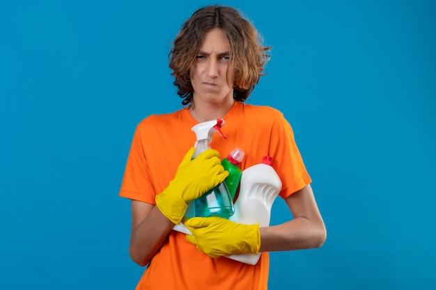 Junger mann im orangefarbenen t-shirt, das gummihandschuhe hält, die reinigungswerkzeuge halten, die kamera betrachten, missfiel mit dem stirnrunzelnden gesicht, das über blauem hintergrund steht