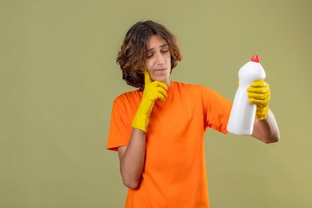 Junger mann im orangefarbenen t-shirt, das gummihandschuhe hält flasche der reinigungsmittel hält, die es mit nachdenklichem ausdruck auf gesicht denkend betrachten, das über grünem hintergrund steht