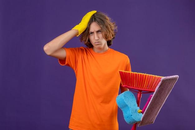 Junger mann im orangefarbenen t-shirt, das gummihandschuhe trägt, die schwamm und mops halten, die mit hand auf kopf für fehler stehen, der sehr besorgt über lila hintergrund schaut
