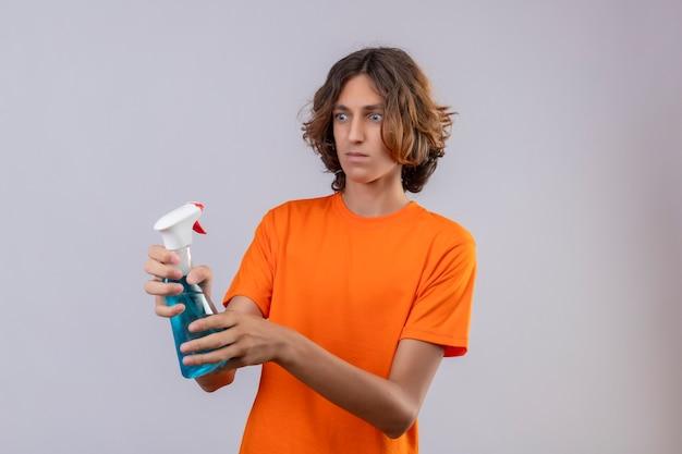 Junger mann im orangefarbenen t-shirt, der reinigungsspray hält, das es überrascht und verwirrt betrachtet, über weißem hintergrund stehend