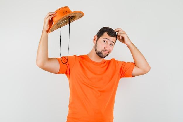 Junger mann im orangefarbenen t-shirt, der seinen hut abnimmt, den kopf kratzt und nachdenklich aussieht, vorderansicht.