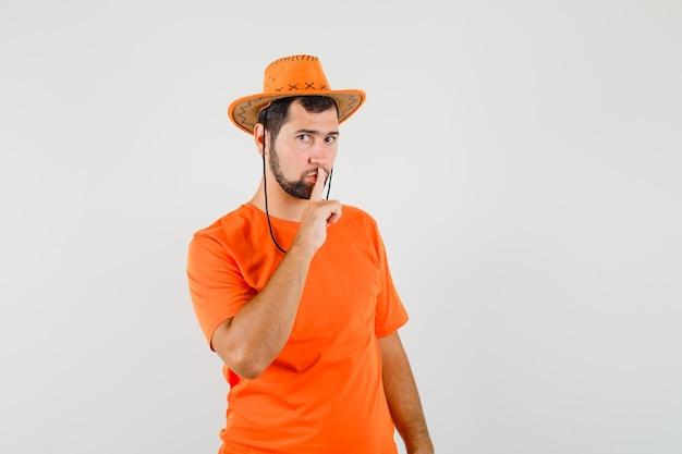 Junger mann im orangefarbenen t-shirt, hut, der stille zeigt und vorsichtig aussieht, vorderansicht.