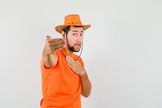 Junger mann im orangefarbenen t-shirt, hut, der zum kommen einlädt, vorderansicht.