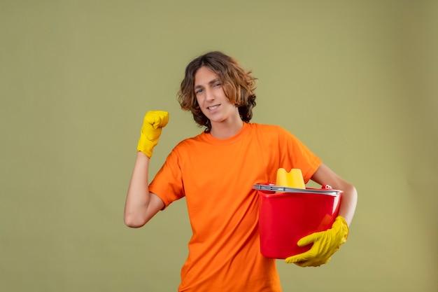 Junger mann im orangefarbenen t-shirt mit gummihandschuhen, die einen eimer mit reinigungswerkzeugen halten, die die faust ballen und sich über seinen erfolg und sieg freuen und über grünem hintergrund glücklich stehen
