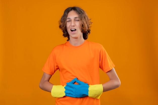 Junger mann im orangefarbenen t-shirt mit gummihandschuhen, die lachend seinen bauch berührend über gelbem hintergrund tragen