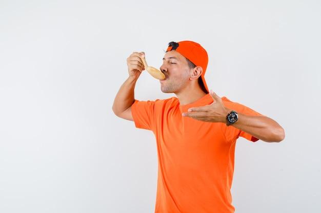 Junger mann im orangefarbenen t-shirt und in der kappe, die mahlzeit mit holzlöffel essen und hungrig schauen